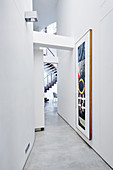Painting in long, narrow, white corridor in architect-designed house