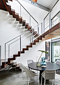 Round dining table and upholstered chairs below cantilever staircase