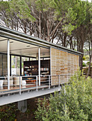 Modern architect-designed house on stilts with open façade in woods