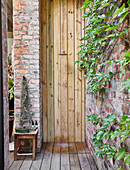 Outside shower with wooden wall next to climber-covered brick wall