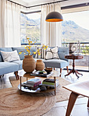Pale blue sofa and panoramic windows in classic living room