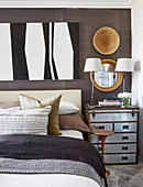 Steamer trunk with metal fittings used as bedside table in bedroom with ethnic accessories