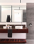 Clear lines and wooden washstand in masculine bathroom