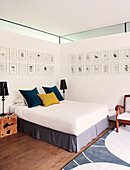 Bedroom with gallery of pictures on two walls and clerestory windows