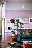 Gallery of pictures on pink wall in artistic living room