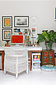 Wicker chair at desk below gallery of pictures on wall in room with exotic accessories