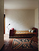 Couch and rug with ethnic textiles against roughly rendered walls