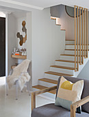 Armchair and plexiglas chair with sheepskin blanket at foot of modern staircase with wooden treads