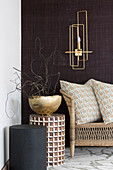 Round side tables and golden bowl below sconce lamp on dark wall