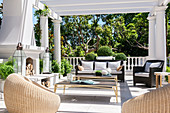 Elegant terrace with wicker armchairs, coffee table, sofa and fireplace