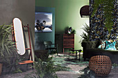 Coat stand with mirror, seating, chest of drawers and plants in the room with green walls