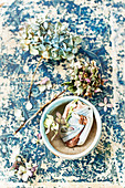 Dried hydrangea flowers and ceramic shards in bowl on old book cover