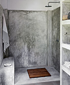 Simple shower with polished cement wall in the garden house