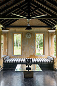 Sri Lanke mask on glass-topped table, striped bed in garden pavilion