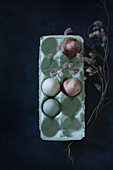 Dried flowers around painted eggs in egg box