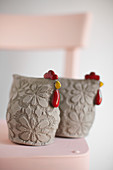 Two ceramic hens with embossed floral patterns