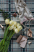 Vest, notepad and white tulips on tartan surface