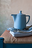 Blue coffee pot and stacked cloths on stool