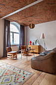 Leather sofa and designer leather chairs in open-plan interior with brick ceiling