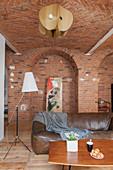 Coffeetable, Ledersofa und Stehlampe in offenem Wohnraum mit Ziegelwand