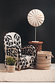 Patterned armchair, fabric basket and side table in front of black wall