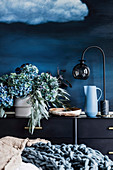 Vase with hydrangeas and eucalyptus branches, bowl, jug and table lamp on sideboard against blue wall