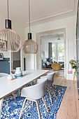 Pendant lamps above dining table and shell chairs with view into living room through open double doors