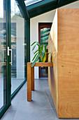 Zimmerpflanze auf in Holzblock intergriertem Tisch in modernem Wintergarten