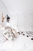 Blick über Doppelbett auf Einbauschränke in weißem Schlafzimmer