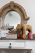 Old toy bear on wheels in front of oval mirror with wooden frame