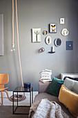 Polstersofa, Beistelltisch und Dekoobjekte an dunkler Wand im Altbau-Wohnzimmer