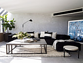 Elegant, black upholstered suite with pillows and coffee table, large-format picture in the background