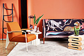 Designer sofa with animal-patterned upholstery, side table, ladder, armchair and coffee table in living room with orange wall