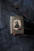 Tea caddy with silhouette ornamentation under tulle on crumpled black fabric