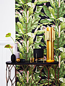 Black and gold ornaments on table against wall with leaf-patterned wallpaper