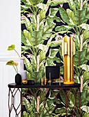 Tisch mit schwarzer und goldener Deko vor Wand mit Blattmuster