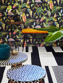 Patterned stools and upholstered bench in front of wall with floral wallpaper