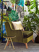 Gilt stool and green velvet armchair in front of leaf-patterned wallpaper