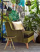Goldener Hocker und grüner Samtsessel vor Tapete mit Blattmotiv