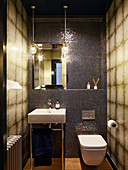 Toilet and various tiled in shades of brown in small bathroom