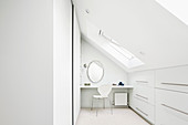 Bright, white attic room with fitted cupboards