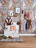 Hanging cloakroom in front of a wallpaper with fairytale wildlife