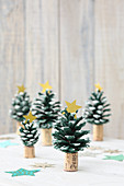 Christmas trees hand-crafted from pine cones painted green stuck on corks
