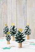 Gebastelte Weihnachtsbäume aus grün bemalten Zapfen auf Korken