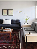 Two different sofas, side table, standard lamp and coffee table on rug in living room