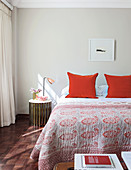 Red-patterned bedspread and red pillows on double bed in bright bedroom