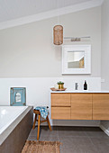 Vanity with wooden front, wooden stool and bathtub in the bathroom with light gray wall