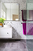 Mirror cabinet, vanity unit and towel rack in tiled bathroom