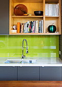 Fitted kitchen with gray base cabinet, green splash guard and open shelf
