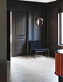 Schlichter Sessel vor grauer Wand mit Kassettenverkleidung